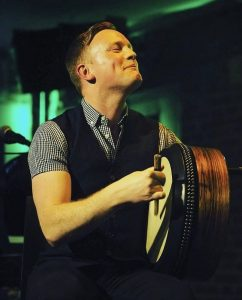 bodhran player Adam Brown playing at a live gig on a stage